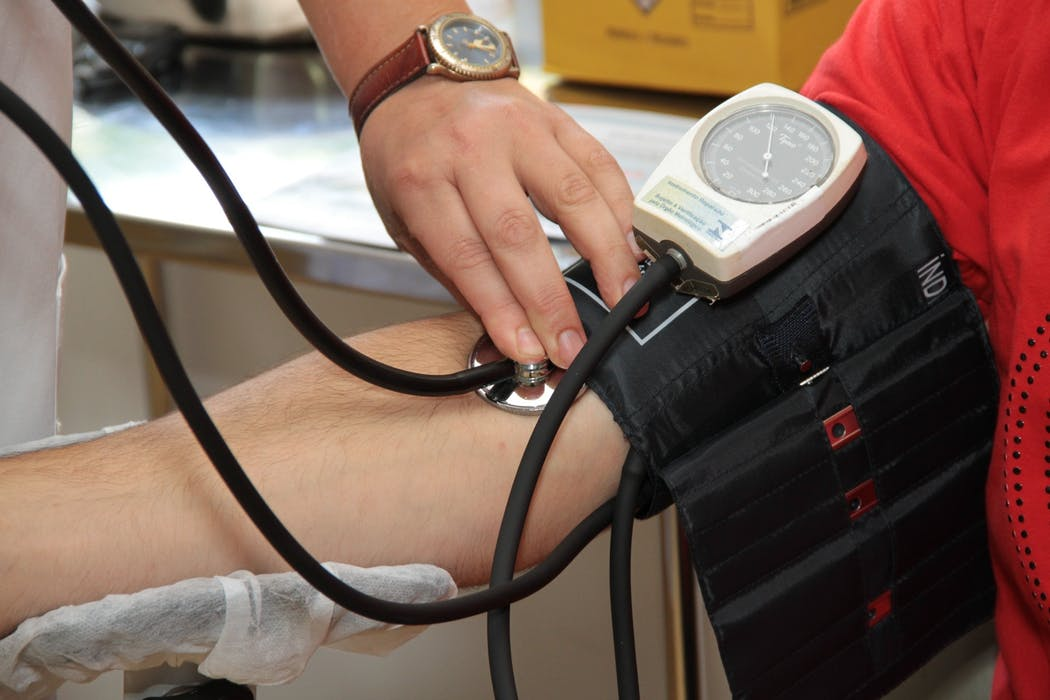 doctor checking a patient's blood pressure